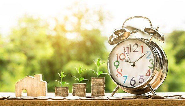 Stacks of coins with plants sprouts and clock