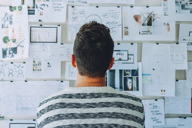 Man staring at wall of papers